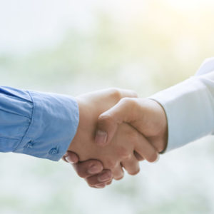 Business partners shaking hands to confirm the deal