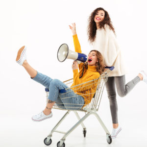 Two happy girls in sweaters having fun with shopping trolley and megaphone over white background